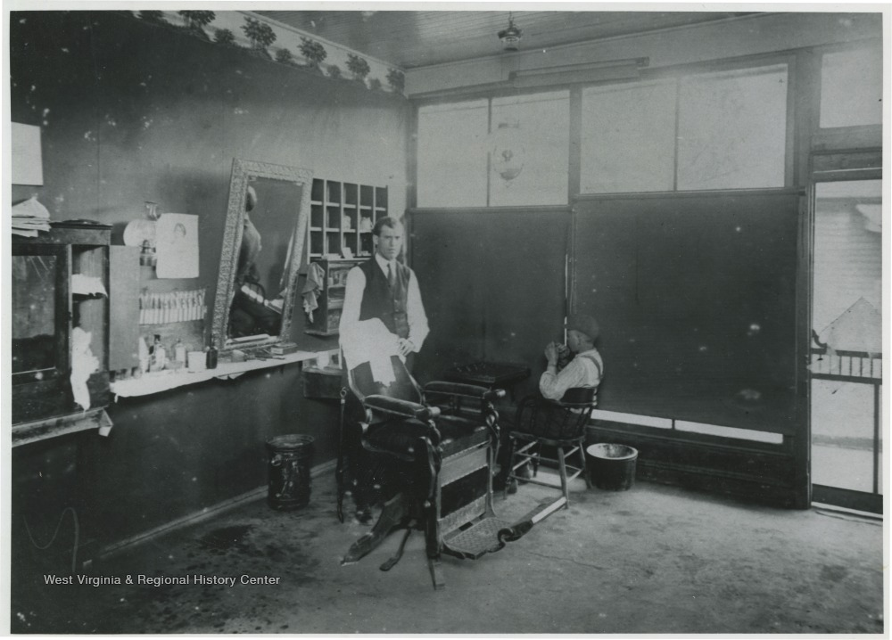A barber poses by a chair inside the shop.